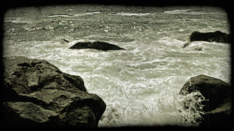 Waves crash against rocks. Vintage stylized video clip Footage