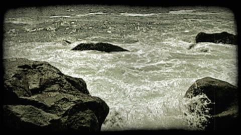 Waves crash against rocks. Vintage stylized video clip Footage