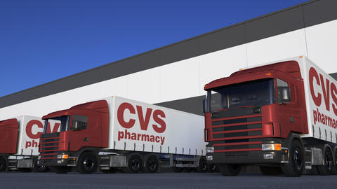 Freight semi trucks with CVS Health logo loading or unloading at warehouse dock Footage