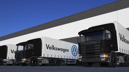 Freight semi trucks with Volkswagen logo loading or unloading at warehouse dock Live Action