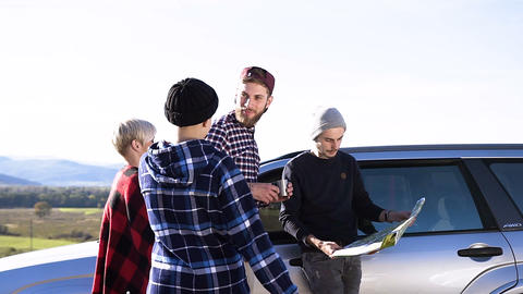 adventure friends standing beside car looking in map checking directions of trip Footage