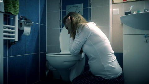 Young woman vomiting in bathroom wc - morning sickness during pregnancy ビデオ