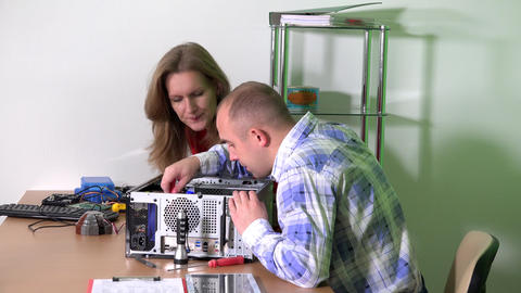 Technician man with colleague woman upgrade computer components at repair office GIF
