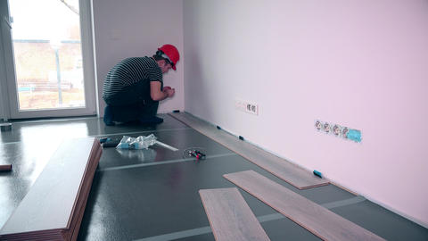 Man laying laminate flooring in construction Footage