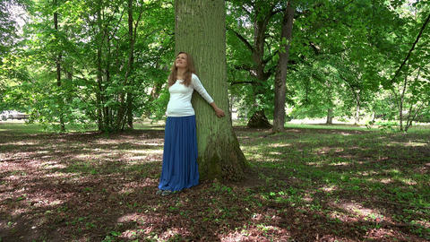 Relaxed pregnant woman standing lean on big tree trunk in park ビデオ