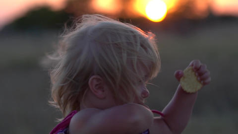 Young girl in the field during sunset. Little girl at sunset close-up Footage