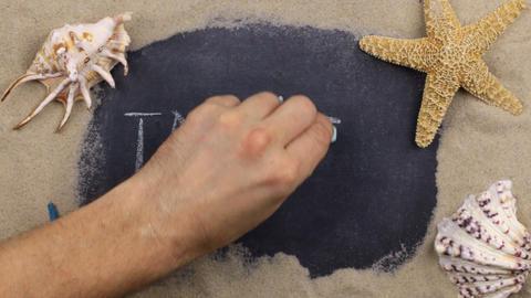 Handwritten word TAHITI written in chalk, among seashells and stars. Top view Live Action
