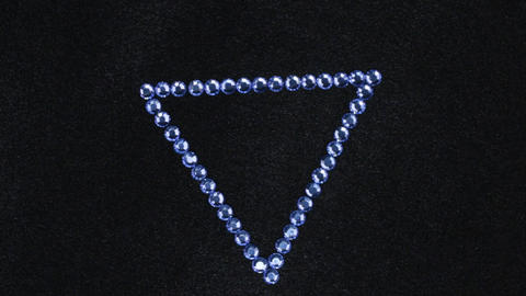 Rotation of a triangle made of blue rhinestones on black fabric, the triangle Live Action