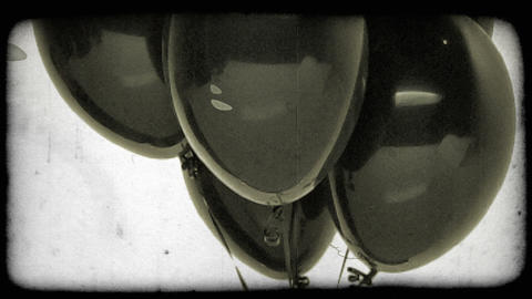 Black balloons with tilting shot. Vintage stylized video clip Footage