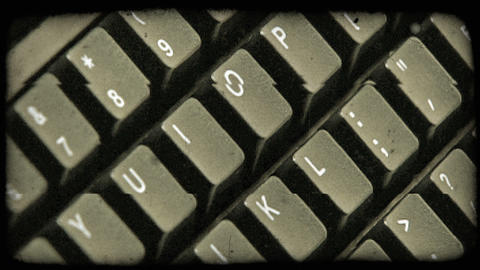 Vertical shot of keyboard from one end to the other coming in and out of focus.  Footage