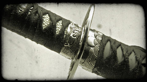 Close-up shot of a katana sword being pulled out of its sheath. Vintage stylized Footage