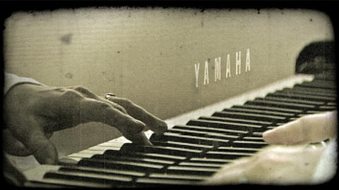 Zooming out shot of hands playing the piano. Vintage stylized video clip Footage