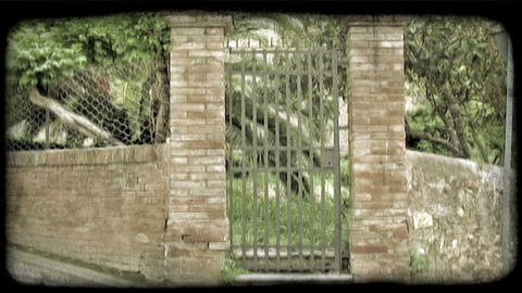 Static shot of a gate and fence of a property in Italy. Vintage stylized video c Footage