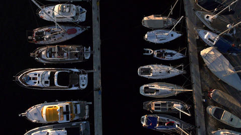Aerial, vertical - Marina docks with boats docked and sailing boats at sunset Live Action