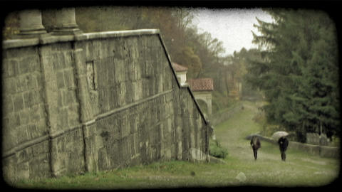 Static shot of a structure and two people going up a hill. Vintage stylized vide Live Action