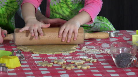 little mother helper girl is helping to roll dough batter on kitchen table Footage