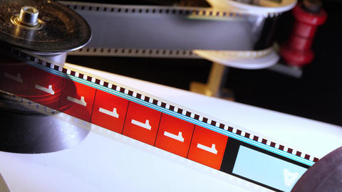 Close up of a moving 35mm film stripe in a movie theater Footage