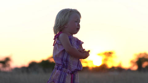 Crying little girl alone in the meadow. Child at sunset in the meadow Footage
