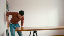 Carpenter Man is Finishing Wooden Oak Table with Roller and Varnish Oil at Home Footage