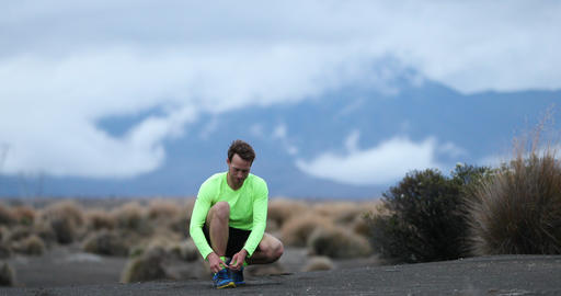 Runner man tying running shoes and runs on trail outdoors Footage