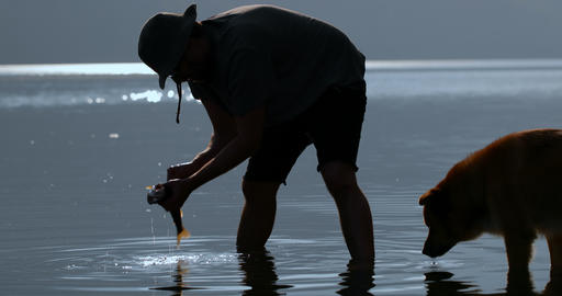 Fisherman cleaning a dead fish in the river 4k Live Action
