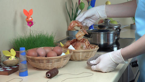 woman hand prepare Easter eggs dyed with onion shell kitchen. 4K Footage