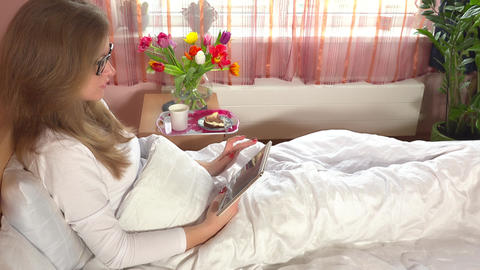 Woman sitting in bed using tablet computer. Breakfast and flowers on cupboard ビデオ