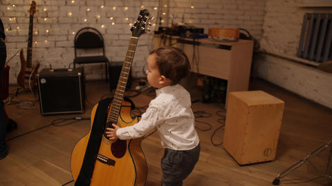 Curious baby boy gently makes a sound on classical guitar strings with his Live Action