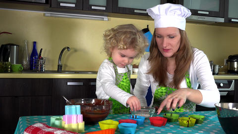 Adorable child decorating muffin cups. Little helper girl with mother ビデオ