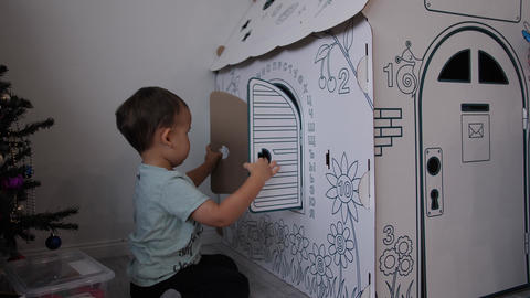 Child and paper house. Baby opens and closes a cardboard window on a wall with Footage