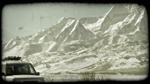 SUV near mountains. Vintage stylized video clip Live Action