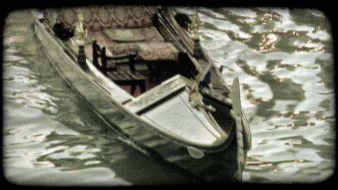 Static shot of a gondolier maneuvering his gondola in the water. Vintage stylize Footage