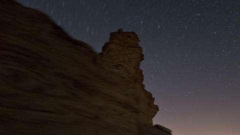 Tracking footage of desert rock formation, and cosmos moving in the sky above. C Live Action