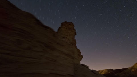 Panning shot of Tracking footage of desert rock formation, and cosmos moving in  Footage