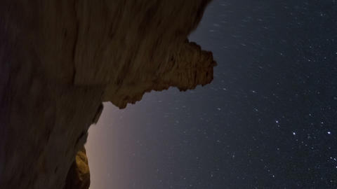Vertical shot of Tracking footage of desert rock formation, and cosmos moving in Live Action