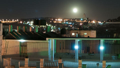 Time lapse of moonrise over Israeli rooftops. Cropped Footage
