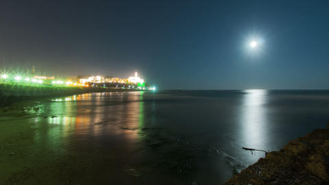 Panning shot of Beach footage of moon setting into the ocean near an Israeli cit Footage