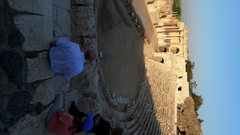 Vertical shot of Time lapse of tour groups in an ancient Roman amphitheater Footage