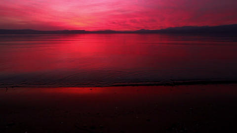 Stock Footage of a bright sunset reflecting off of the Sea of Galilee in Israel Footage