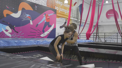The coach teaches the novice acrobat how to land on a trampoline Footage