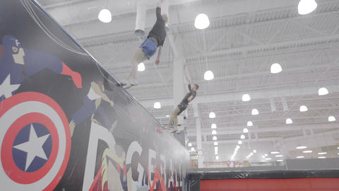 Two acrobats jump onto a wall using a trampoline Footage