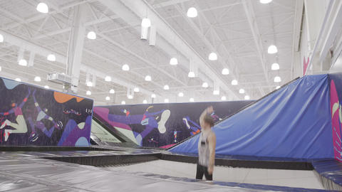 Sportsman is performing acrobatic elements on a trampoline Footage