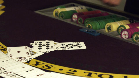 Dealing cards onto a gambling table with chips Footage