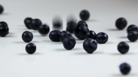 Blueberries being dropped onto a table Footage