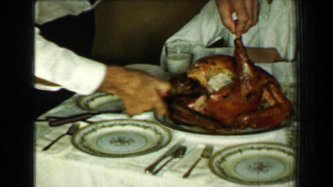 1958: Man carving Thanksgiving dinner turkey removes drumstick leg Footage