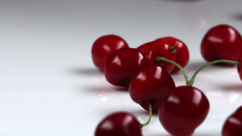 Red cherries dropping onto a table Footage