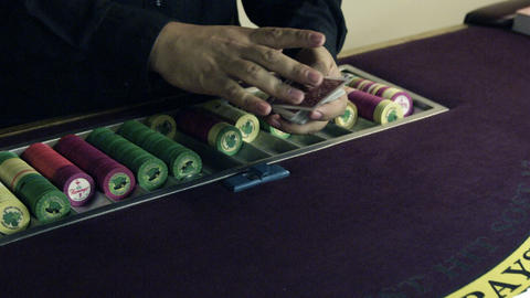 Dealer shuffling and dealing cards onto a table Footage