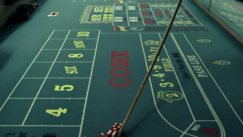 Moving dice across a craps table with the stick Footage