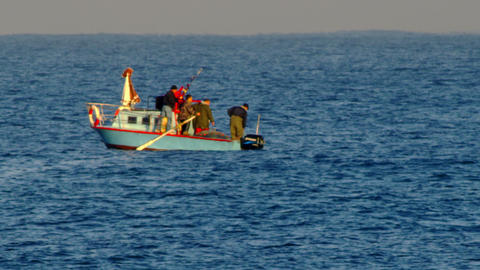 Stock Video Footage of a surfer and fishing boat on the Mediterranean shot in Is Footage