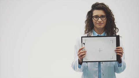 Smiling female doctor with a folder in a single standing. Smiling woman - a Footage